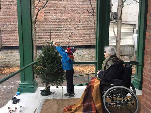 Photo of Sharon Holcroft sitting on the porch of the Fulford Residence with her grandson placing an item on a small spruce tree.